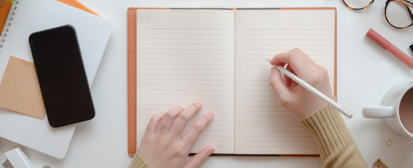 Image showing two hands and someone writing in a notebook